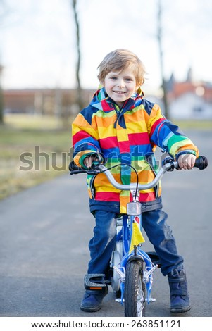 Happy cute blond boy in colorful raincoat riding his first bike and having fun on warm  day, outdoors. Active leisure with children in winter, sping or autumn. - stock photo
