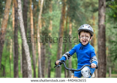 Happy cute blond kid boy having fun his first bike on sunny summer day, outdoors. Happy child making sports. Active leisure for children.Kid boy wear safety helmet. boy is smiling and cicling. - stock photo