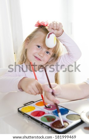 happy cute blonde hair little girl 4 or 5 years old in sweet face expression painting  traditional Easter eggs on a white table backlight and white window in the background