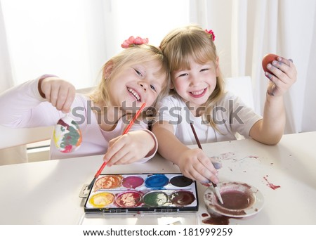 happy cute blonde hair little girls 4 or 5 years old with sweet face expression having fun together painting traditional Easter eggs on a white table backlight and white window in the background - stock photo