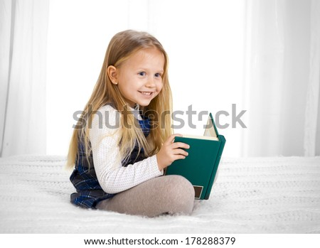 happy cute blonde haired school girl wearing a school uniform reading a book sitting on bed sofa - stock photo