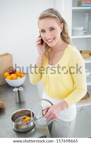 Happy cute blonde phoning and making dinner in bright kitchen - stock photo