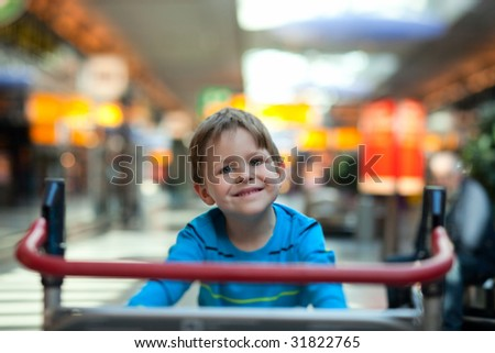 Happy cute boy at airport riding on luggage cart - stock photo