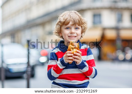 Happy cute boy on a street of city eating fresh croissant, on warm day. Paris, France. - stock photo