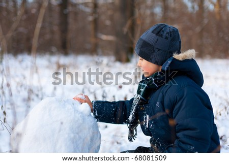 Happy cute boy playing in the snow near a forest
