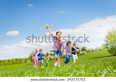Happy cute boy with plane toy and chasing him kids - stock photo