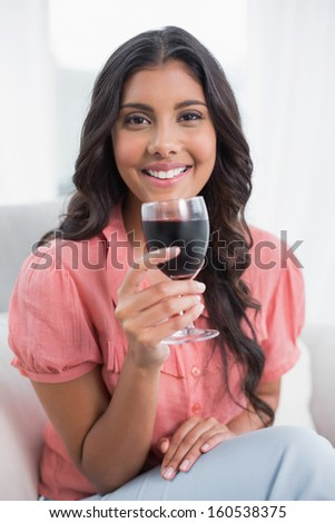 Happy cute brunette sitting on couch holding wine glass in bright living room