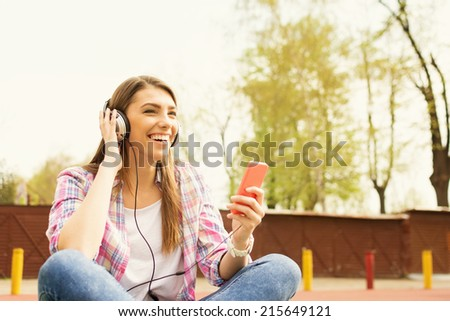 Happy cute Caucasian teenage girl with headphones and smartphone in park listening to music, sitting and laughing. Candid shot. - stock photo
