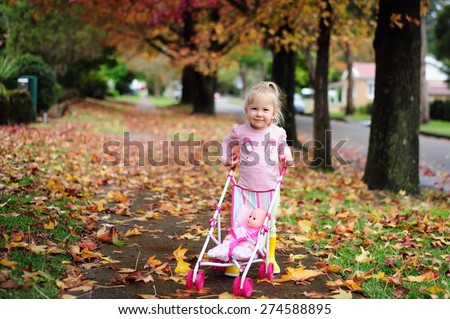 Happy cute child, adorable toddler or baby girl going for a walk with a doll pram and a doll in it in a beautiful park with autumn trees and leaves - stock photo
