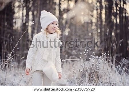 Happy cute child girl in white outfit walking in snowy winter forest - stock photo