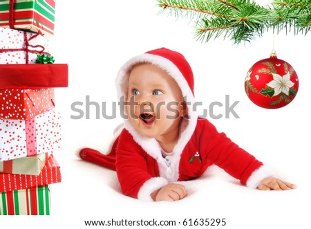 Happy, cute Christmas  baby under a tree branch with bauble and gifts isolated on white. - stock photo