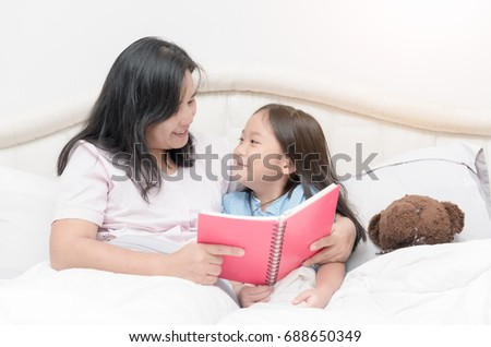 Happy cute daughter looking mother reading book on bed, concept eduaction