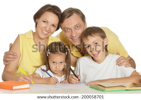 Happy cute family doing homework at table - stock photo