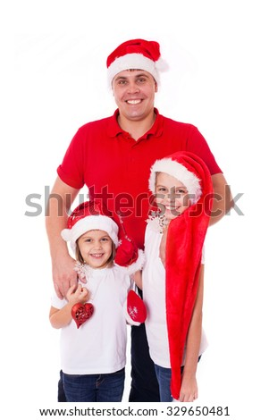 Happy cute family father and two daughters sisters in santa's hats laughing