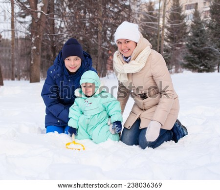 Happy cute family mother woman girl with baby boy kid and teenager playing in park in winter - stock photo