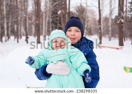 Happy cute family teenager playing  with baby boy kid brother in park in winter - stock photo