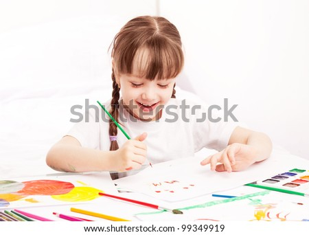 happy cute five year old girl sitting by the table and  painting with watercolor at home - stock photo
