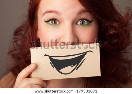 Happy cute girl holding paper with funny smiley drawing on gradient background - stock photo