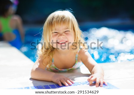 happy cute girl in outdoor swimming pool has fun with splash and toys - stock photo