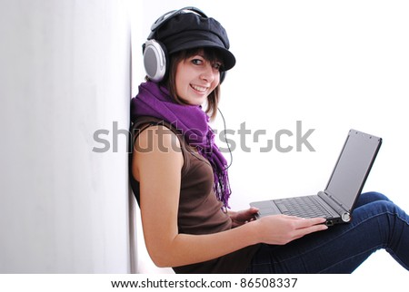 Happy cute girl listening to music on the laptop sitting against wall with laptop - stock photo