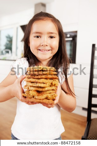 Happy cute girl looking at camera holding stack of freshly baked cookies