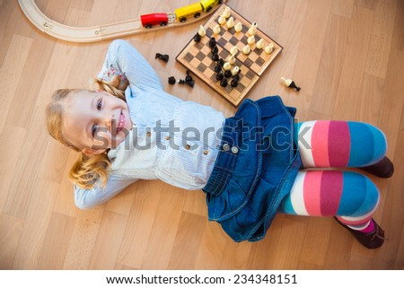 Happy cute girl lying on floor in the room - stock photo