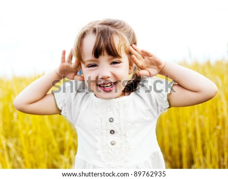 happy cute girl playing and making faces in the wheat field on a warm summer day - stock photo