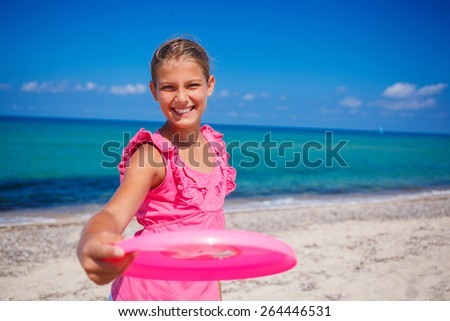 Happy cute girl playing frisbee on beach - stock photo
