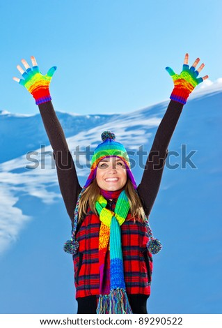 Happy cute girl playing in snow outdoor,looking up with hands up, beautiful woman with raised arms to blue sky & nature,young teen female wearing colorful hat Christmas winter holidays travel vacation