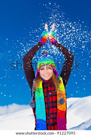 Happy cute girl playing with snow outdoor, throwing it up with hands, beautiful woman smiling with raised arms to blue sky and nature, young teen female in colorful hat, Christmas winter holidays - stock photo