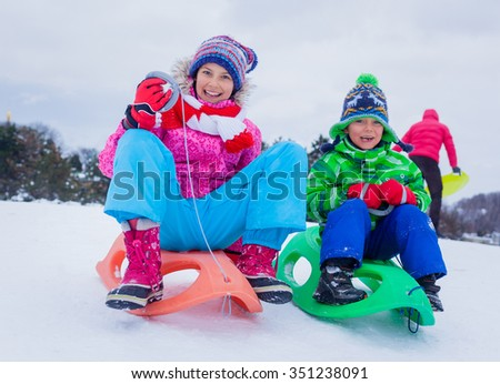 Happy cute girl with her brother sledding in the snow mountain - stock photo