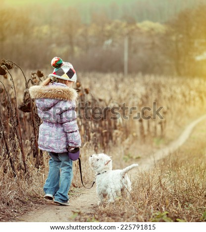 happy cute girl with her dog breed White Terrier walking in a field - stock photo