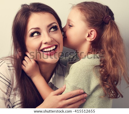 Happy cute kid girl whispering the secret to her laughing happy mother in ear with fun face. Closeup vintage portrait