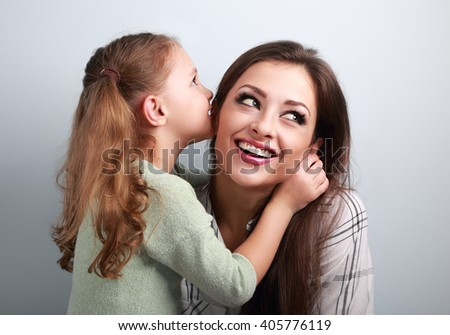 Happy cute kid girl whispering the secret to her smiling mother in ear with fun face on blue background