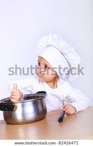 happy cute little baby in a cook cap with a pan - stock photo