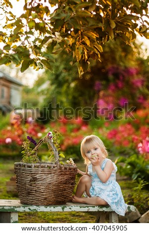 Happy cute little blonde girl two years sitting on the bench under the apple tree next to a basket of flowers and bitten green apple sunset of warm summer days, beautiful light - stock photo