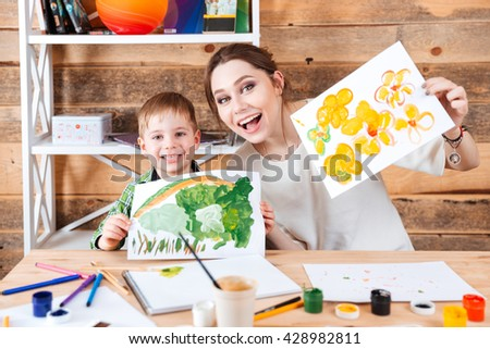 Happy cute little boy and his mother sitting and showing their paints  - stock photo