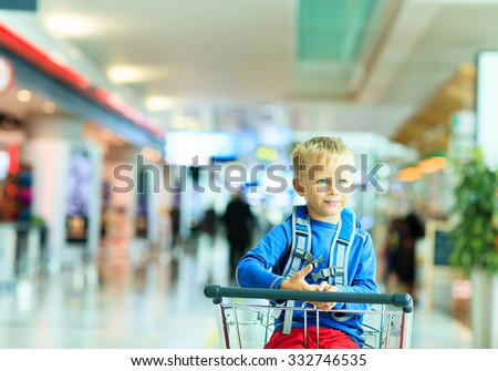 Happy cute little boy at airport riding on luggage cart, kids travel
