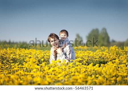 happy cute little boy having fun with his dad in the field of dandelions - stock photo