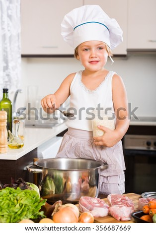 Happy cute little girl cooking with meat at home kitchen