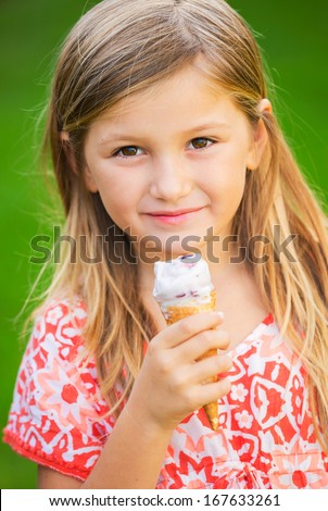 Happy cute little girl eating ice cream cone