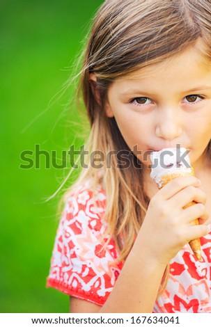 Happy cute little girl eating ice cream cone - stock photo