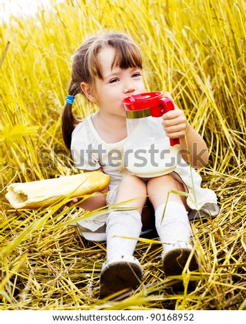 happy cute little girl having a picnic in the wheat field drinking milk and eating a long loaf - stock photo