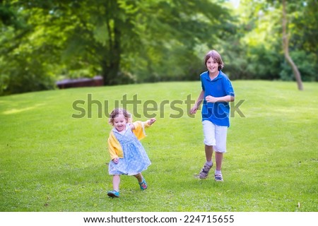 Happy cute little girl in a colorful summer dress and her laughing brother, active teenage boy, running together playing in park on a beautiful warm summer day