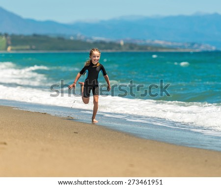 happy cute little girl in a wetsuit running along the coast