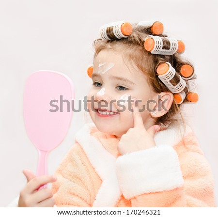 Happy cute little girl in hair curlers with mirror applying cream isolated on a white - stock photo