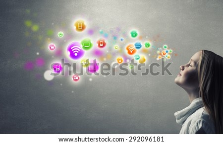 Happy cute little girl looking up at colorful icons of different entertainment apps