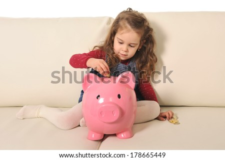 Happy Cute little girl playing putting coin into huge piggy bank on sofa - stock photo