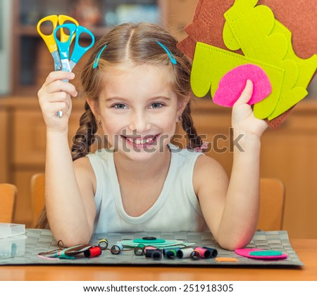 happy cute little girl shows scissors and materials for needlework - stock photo