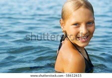 Happy Cute little girl swimming in water - stock photo